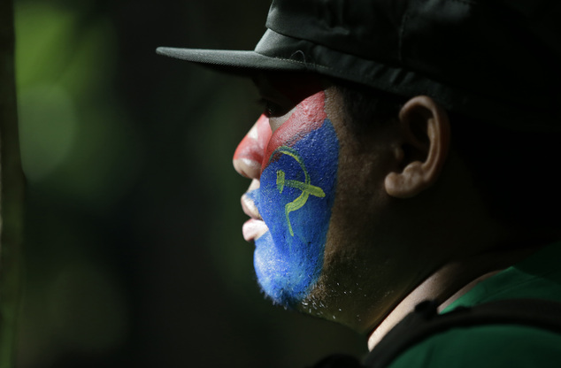 In this photo taken Nov. 23, 2016, a member of the New People's Army communist rebels with face painted to conceal his identity, stands in formation during ceremonies held at their guerrilla encampment tucked in the harsh wilderness of the Sierra Madre mountains southeast of Manila, Philippines. Communist guerrillas warn that a peace deal with President Rodrigo Duterte's government is unlikely if he won't end the Philippines' treaty alliance with the United States and resist control by other countries. (AP Photo/Aaron Favila)