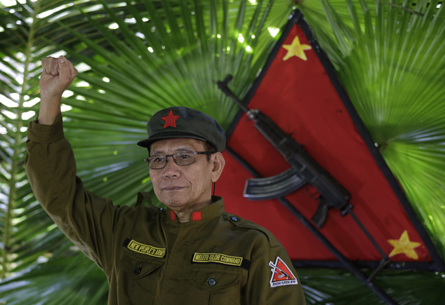 In this photo taken Nov. 23, 2016, New People's Army new regional rebel commander and spokesman Jaime Padilla, who uses the nom de guerre Comrade Diego, raises his clenched fists after a clandestine news conference in a encampment tucked in the harsh wilderness of the Sierra Madre mountains southeast of Manila, Philippines. Communist guerrillas warn that a peace deal with President Rodrigo Duterte's government is unlikely if he won't end the Philippines' treaty alliance with the United States and resist control by other countries. (AP Photo/Aaron Favila)