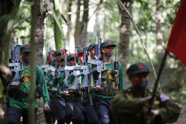 In this photo taken Nov. 23, 2016, members of the New People's Army communist rebels march during the entry of colors as part of ceremonies before a clandestine news conference held at their guerrilla encampment tucked in the harsh wilderness of the Sierra Madre mountains southeast of Manila, Philippines. Communist guerrillas warn that a peace deal with President Rodrigo Duterte's government is unlikely if he won't end the Philippines' treaty alliance with the United States and resist control by other countries. (AP Photo/Aaron Favila)