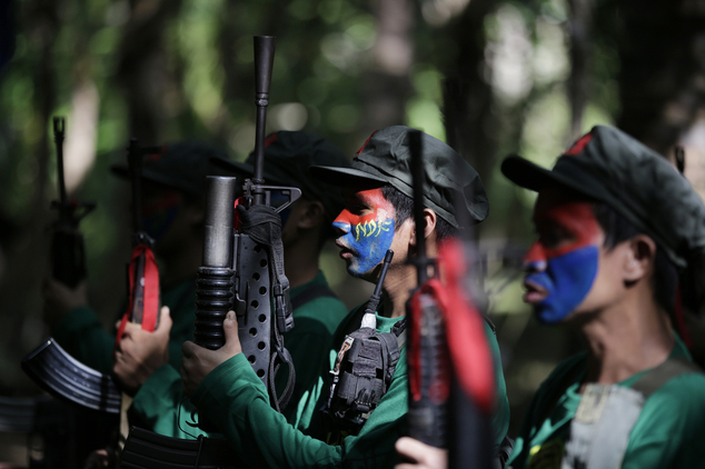 In this photo taken Nov. 23, 2016, members of the New People's Army communist rebels with face painted to conceal their identities, hold their weapons during ceremonies before a clandestine news conference held at their guerrilla encampment tucked in the harsh wilderness of the Sierra Madre mountains southeast of Manila, Philippines. Communist guerrillas warn that a peace deal with President Rodrigo Duterte's government is unlikely if he won't end the Philippines' treaty alliance with the United States and resist control by other countries. (AP Photo/Aaron Favila)