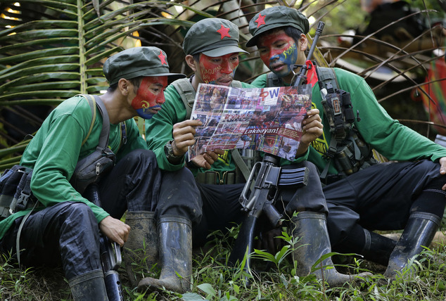 In this photo taken Nov. 23, 2016, members of the New People's Army communist rebels with face painted to conceal their identities, reads a local paper at their guerrilla encampment tucked in the harsh wilderness of the Sierra Madre mountains southeast of Manila, Philippines. Communist guerrillas warn that a peace deal with President Rodrigo Duterte's government is unlikely if he won't end the Philippines' treaty alliance with the United States and resist control by other countries. (AP Photo/Aaron Favila)