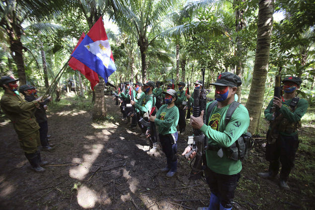 In this photo taken Nov. 23, 2016, members of the New People's Army communist rebels, with face painted to conceal their identities, stand in formation during ceremonies before a news conference held at their guerrilla encampment tucked in the harsh wilderness of the Sierra Madre mountains southeast of Manila, Philippines. Communist guerrillas warn that a peace deal with President Rodrigo Duterte's government is unlikely if he won't end the Philippines' treaty alliance with the United States and resist control by other countries. (AP Photo/Aaron Favila)