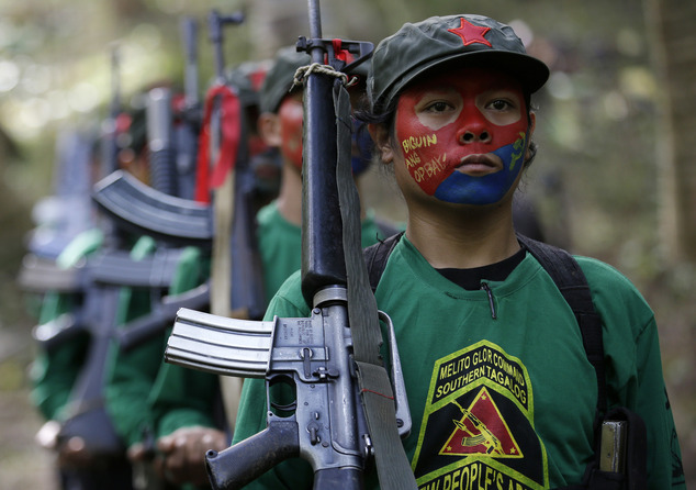 In this photo taken Nov. 23, 2016, members of the New People's Army communist rebels with face painted to conceal their identities, march with their firearms before a news conference held at their guerrilla encampment tucked in the harsh wilderness of the Sierra Madre mountains southeast of Manila, Philippines. Communist guerrillas warn that a peace deal with President Rodrigo Duterte's government is unlikely if he won't end the Philippines' treaty alliance with the United States and resist control by other countries. (AP Photo/Aaron Favila)