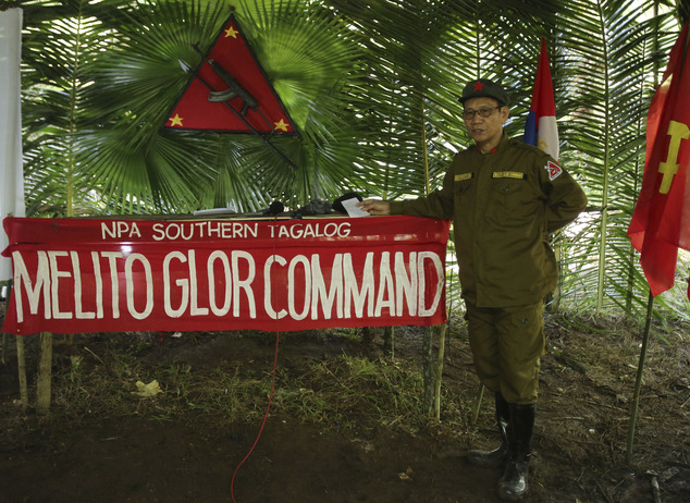 In this photo taken Nov. 23, 2016, New People's Army new regional rebel commander and spokesman Jaime Padilla, who uses the nom de guerre Comrade Diego, answers questions from reporters during a clandestine news conference in their encampment tucked in the harsh wilderness of the Sierra Madre mountains southeast of Manila, Philippines. Communist guerrillas warn that a peace deal with President Rodrigo Duterte's government is unlikely if he won't end the Philippines' treaty alliance with the United States and resist control by other countries. (AP Photo/Aaron Favila)